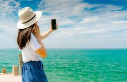 De jonge Aziatische hoed die van de vrouwenslijtage in toevallige smartphone van het stijlgebruik selfie bij pijler nemen De zome royalty-vrije stock afbeeldingen