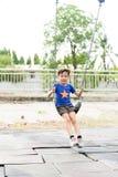 de jonge Aziatische jongen speelt ijzerketting het slingeren Royalty-vrije Stock Afbeelding