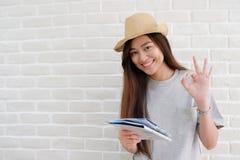 De jonge Aziatische kaart van de vrouwenholding en het glimlachen met o.k. Si van de gusterhand stock foto