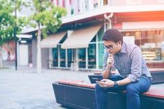 De jonge Aziatische knappe zakenman concentreerde zich terwijl het lezen van van hem Stock Afbeelding