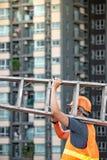 De jonge Aziatische ladder van het de mensen dragende aluminium van de onderhoudsarbeider royalty-vrije stock foto