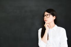 De jonge Aziatische leraar denkt over opeenhoping een goed onderwijs stock afbeelding