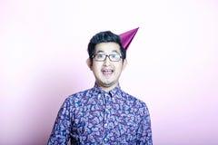 De jonge Aziatische Mens die van Geeky partijhoed dragen Stock Afbeeldingen