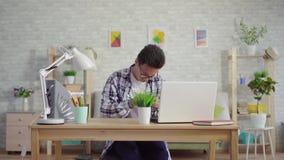 De jonge Aziatische mens in een astmatisch overhemd geniet van de nevel van het hoesten zitting bij laptop stock footage