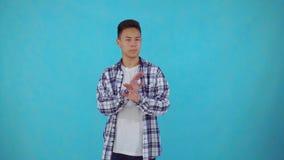 De jonge Aziatische mens toont een ontkenning op blauwe achtergrond stock video