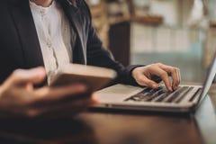 De jonge Aziatische onderneemster kleedde zich strikt in het kostuum die met laptop bij het moderne koffiebinnenland werken royalty-vrije stock foto's