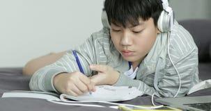 De jonge Aziatische tienerstudent luistert aan muziek en doend thuiswerk thuis, Dolly spruit stock videobeelden