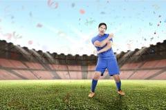 De jonge Aziatische voetbalster viert de kampioen royalty-vrije stock afbeelding