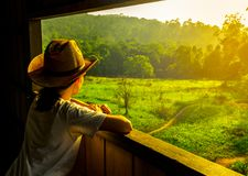 De jonge Aziatische vrouw draagt de hoed zit en het letten op mooie mening van groen grasgebied en bos bij de toren van de het wi stock afbeeldingen