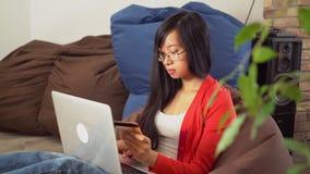 De jonge Aziatische vrouw koopt online op de computerzitting op de kinderspelstoel stock videobeelden