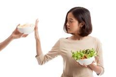 De jonge Aziatische vrouw met salade zegt nr aan chips Stock Afbeeldingen