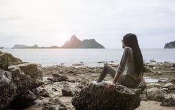 De jonge Aziatische vrouwenzitting op een rots dichtbij het overzees, keek aan het overzees, kou uit de zomer, rusttijd, licht en stock afbeeldingen