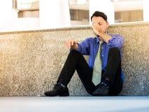 De jonge Aziatische zakenman is gedeprimeerd en beklemtoond, zittend outs Stock Fotografie