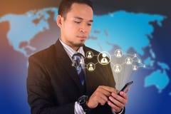 De jonge Aziatische zakenman raakt zijn smartphone met Sociaal de zakenmanpictogram van de Netwerkinterface Royalty-vrije Stock Fotografie