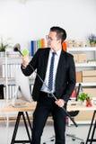 De jonge Aziatische zakenman in zwart kostuum oefent golf in offi uit royalty-vrije stock foto