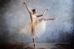 De jonge ballerina in een gouden gekleurd dansend kostuum stelt in een zolderstudio stock afbeelding