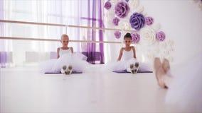 De jonge ballerina's maken van balletoefeningen voor voeten complex herhalen na leraar stock footage
