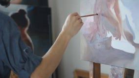 De jonge ballerina zet op balletschoenen en de ballerina bindt schoenen Een kleurrijk palet van olieverf op een triplexraad E stock videobeelden