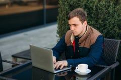 De jonge bankbediende werkt aan laptop bij lunchtijd Stock Afbeeldingen