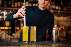 De jonge barman bereidt twee alcoholische cocktails voor, toevoegend stukken van sinaasappel royalty-vrije stock afbeeldingen