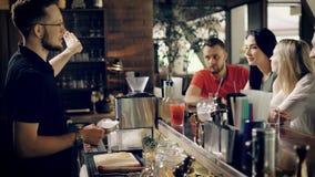De jonge barman voegt ijs aan de cocktail toe om het te koelen een bedrijf van vrienden verwacht hun dranken, willen de vrienden stock videobeelden