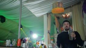De jonge barmannen maken trucs met fles en jigger bij barteller in mist stock videobeelden