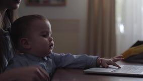 De jonge bedrijfsdame werkt aan laptop thuis terwijl haar leuke kleine baby op haar knie?n zit en speelt met stock video