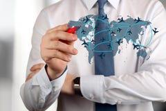 De jonge bedrijfsmens die een vliegtuig trekt leidt op wereldkaart Stock Afbeelding