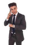 De jonge bedrijfsmens die op de telefoon spreken controleert tijd Royalty-vrije Stock Fotografie