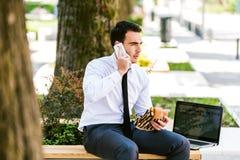 De jonge Bedrijfsmens die op Telefoon spreken terwijl het Eten klemt en het Gebruiken van Laptop stock fotografie