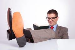 De jonge bedrijfsmens leest een boek met voeten op bureau Royalty-vrije Stock Foto