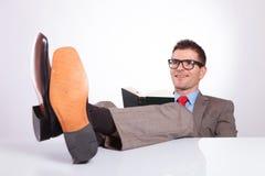 De jonge bedrijfsmens leest met voeten op bureau Royalty-vrije Stock Fotografie