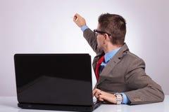 De jonge bedrijfsmens schrijft op de rug terwijl bij laptop Stock Foto's
