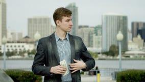 De jonge bedrijfsmens telt zijn geld op een straat van Coronado, San Diego stock videobeelden