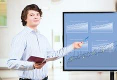De jonge bedrijfsmens toont op de monitorgrafieken Royalty-vrije Stock Afbeeldingen
