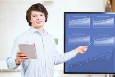 De jonge bedrijfsmens toont op de monitorgrafieken Stock Foto