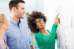 De jonge bedrijfsmensen bespreken aan boord gegevens stock fotografie