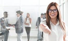 De jonge bedrijfsvrouw bereikt uit voor een handdruk stock foto's