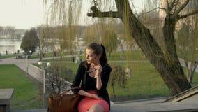 De jonge bedrijfsvrouw die uit een bureaugebouw komen en zit op de treden stock footage
