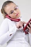 De jonge bedrijfsvrouw draait een telefoonaantal aan vraag Stock Foto's