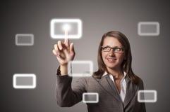 De jonge bedrijfsvrouw drukt een knoopaanraking Stock Afbeeldingen