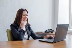 De jonge bedrijfsvrouw is geamuseerd door wat zij op het haar laptop scherm zag royalty-vrije stock afbeeldingen