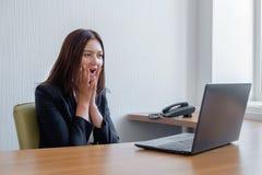 De jonge bedrijfsvrouw is geamuseerd door wat zij op het haar laptop scherm zag royalty-vrije stock fotografie