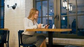 De jonge Bedrijfsvrouw gebruikt Smartphone App en het Drinken Koffie in de Koffie stock videobeelden