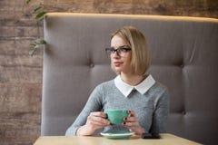 De jonge bedrijfsvrouw in glazen zit in een koffie bij een lijst, drinkt koffie, houdt smartphone in haar hand Het meisje heeft b Royalty-vrije Stock Afbeelding