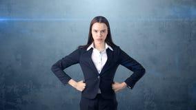 De jonge bedrijfsvrouw in zwart kostuum en wit overhemd is status, houdend haar handen op heupen Het langharige meisje is ernstig stock afbeeldingen
