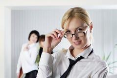 De jonge bedrijfsvrouw op kantoor met collega's stock foto
