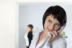 De jonge bedrijfsvrouw op kantoor met collega's Stock Foto's