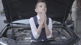 De jonge beklemtoonde goed-geklede jongen die zich voor de gebroken auto met een open kap bevinden De jongen ervaart stock footage