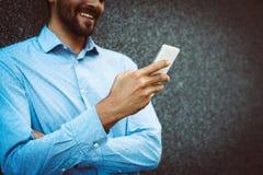 De jonge berichten van de zakenmanlezing op celtelefoon stock fotografie